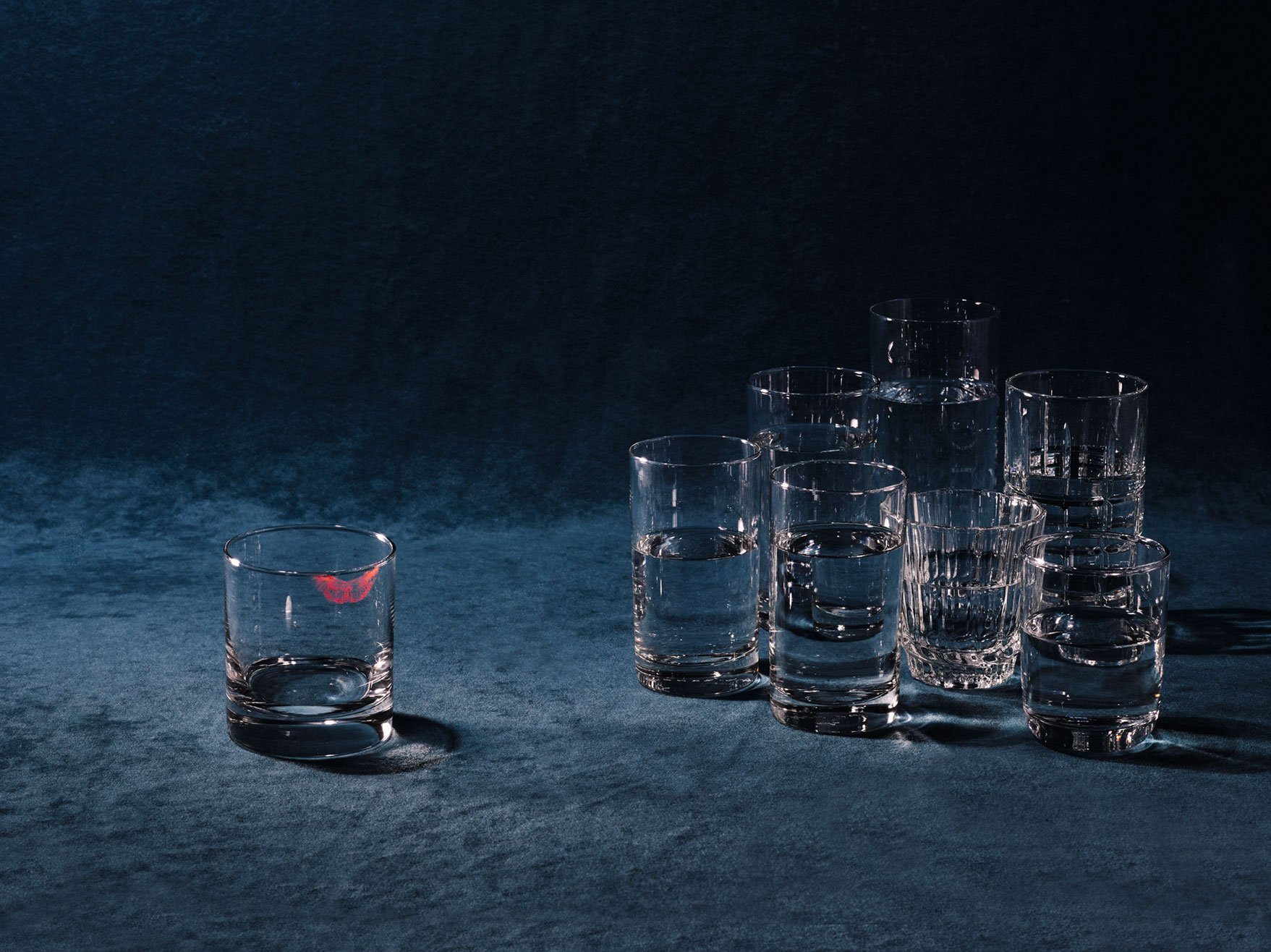 Still life image of various clear cups with one removed from the group and stained with a lipstick kiss for Romance Journal Issue 02 Resistance. Publication design, art direction, print design by RoAndCo.