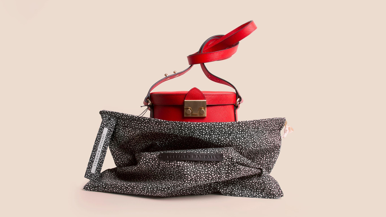 Red Loeffler Randall bucket bag nestled into custom print dust bag. Branding, packaging design and art direction by RoAndCo
