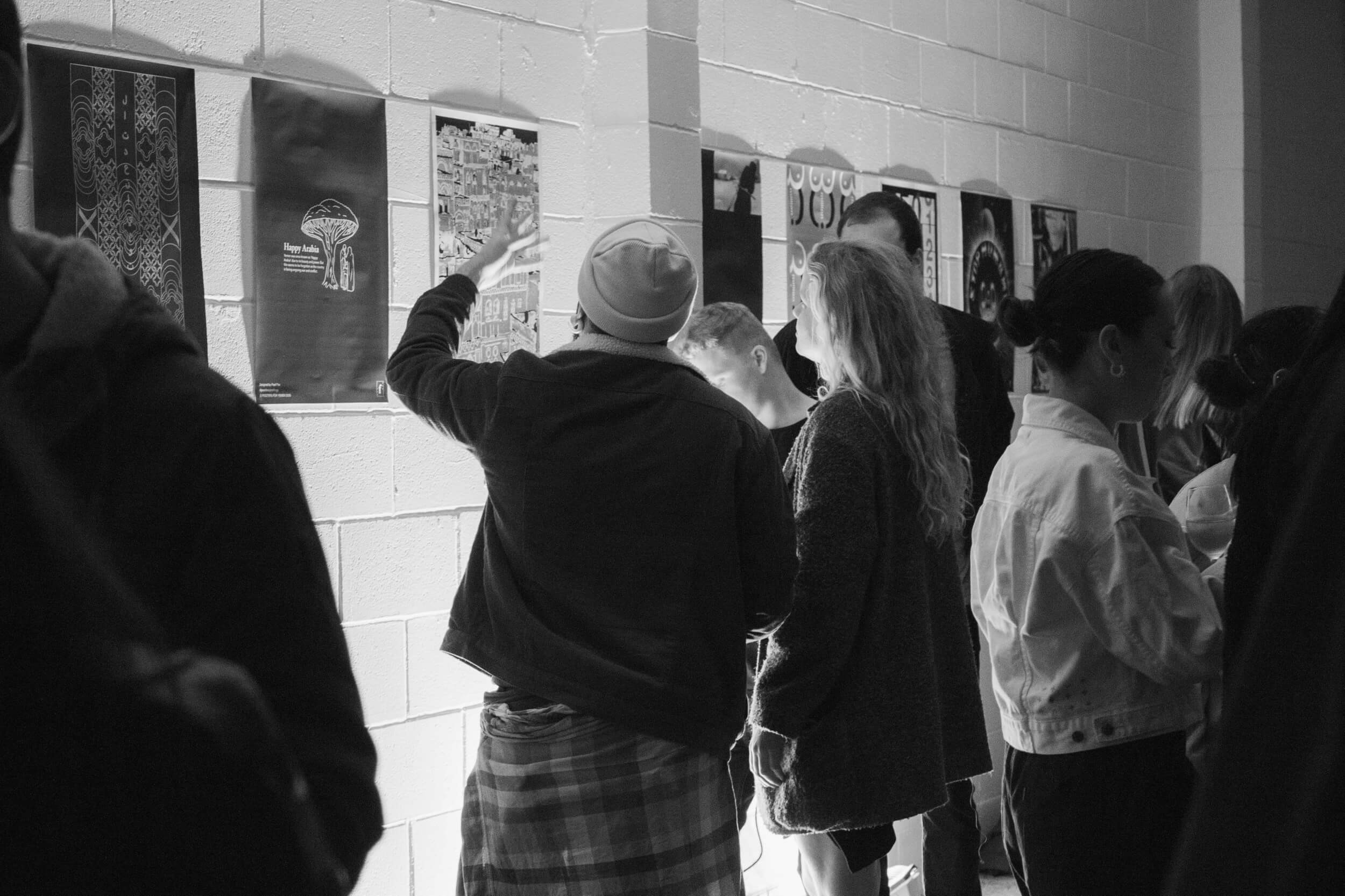People looking at posters on the wall at the Faxed exhibition