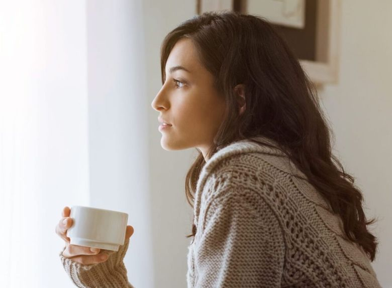 Woman pondering things over a cuppa tea