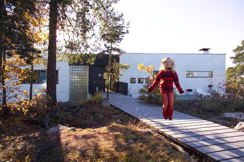 blonde haired child jumping outside a home build with clinka products
