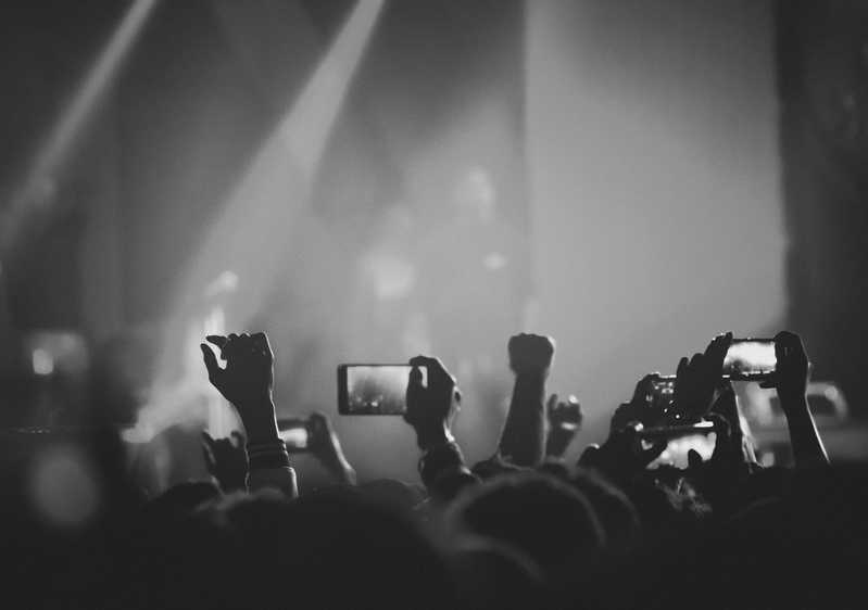 Fans experience a Musicfox artist's next live show with the crowd's mobiles and hands raised.