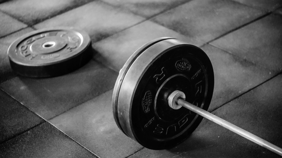 A black and white image of a barbell sits on a stone floor.