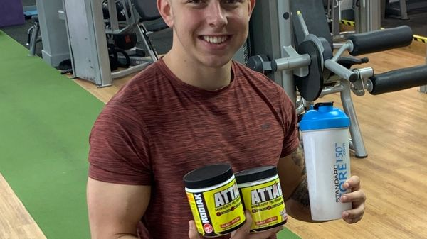 Alex Standing In The Gym Holding Supplements