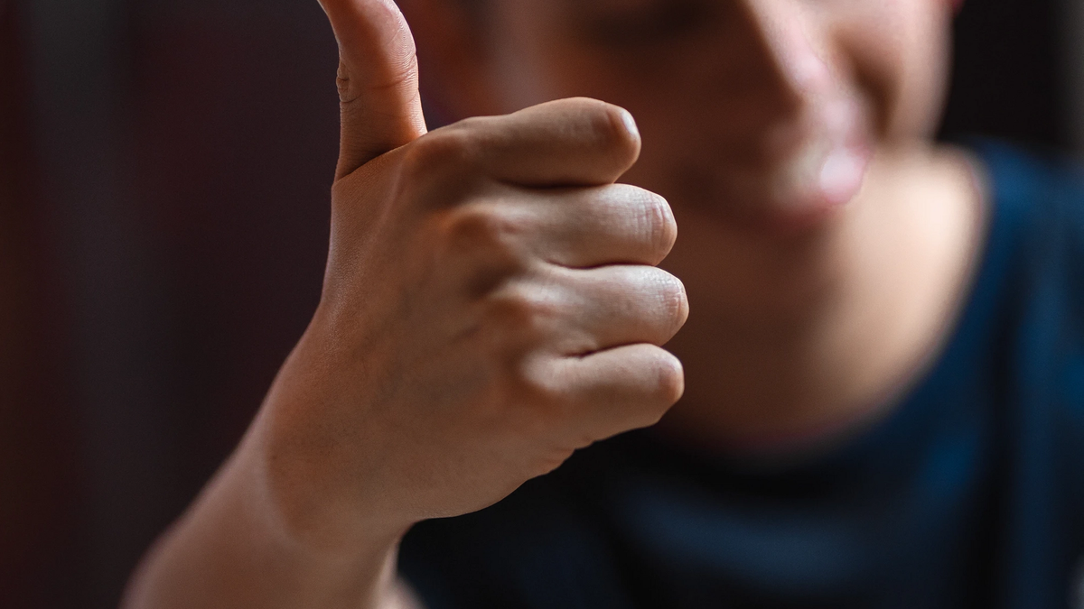 Man putting his thumb up at the camera. The thumb and hand are in focus while the mans face and body are out of focus