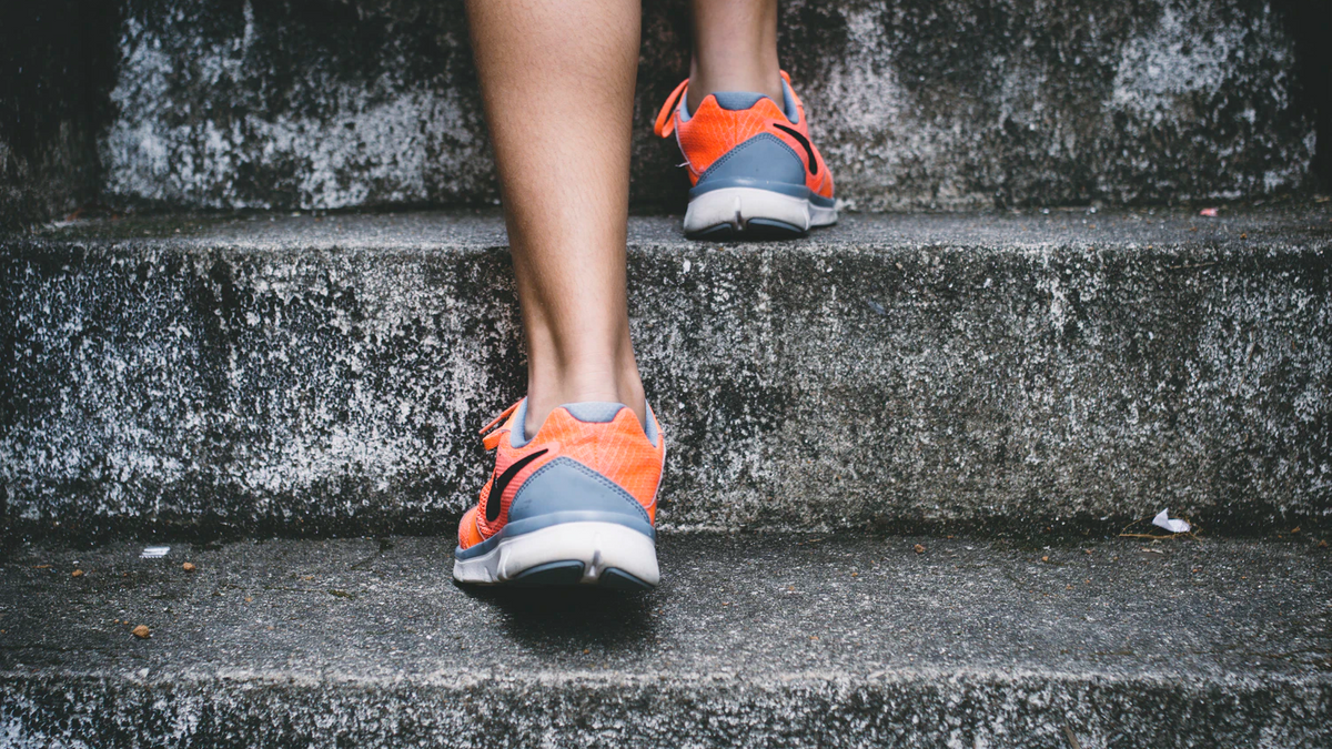 Legs in orange sports shoes walking upstairs