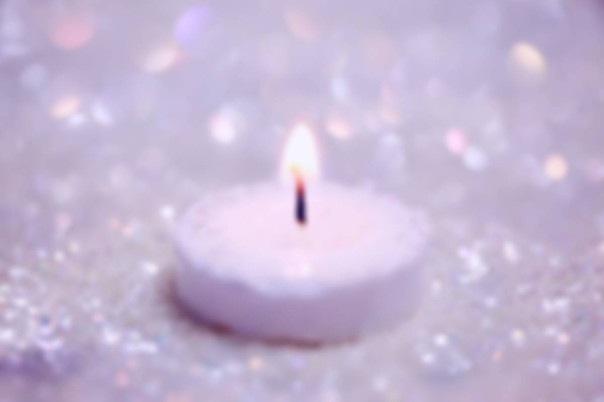 A single lit white candle surrounding by glitter