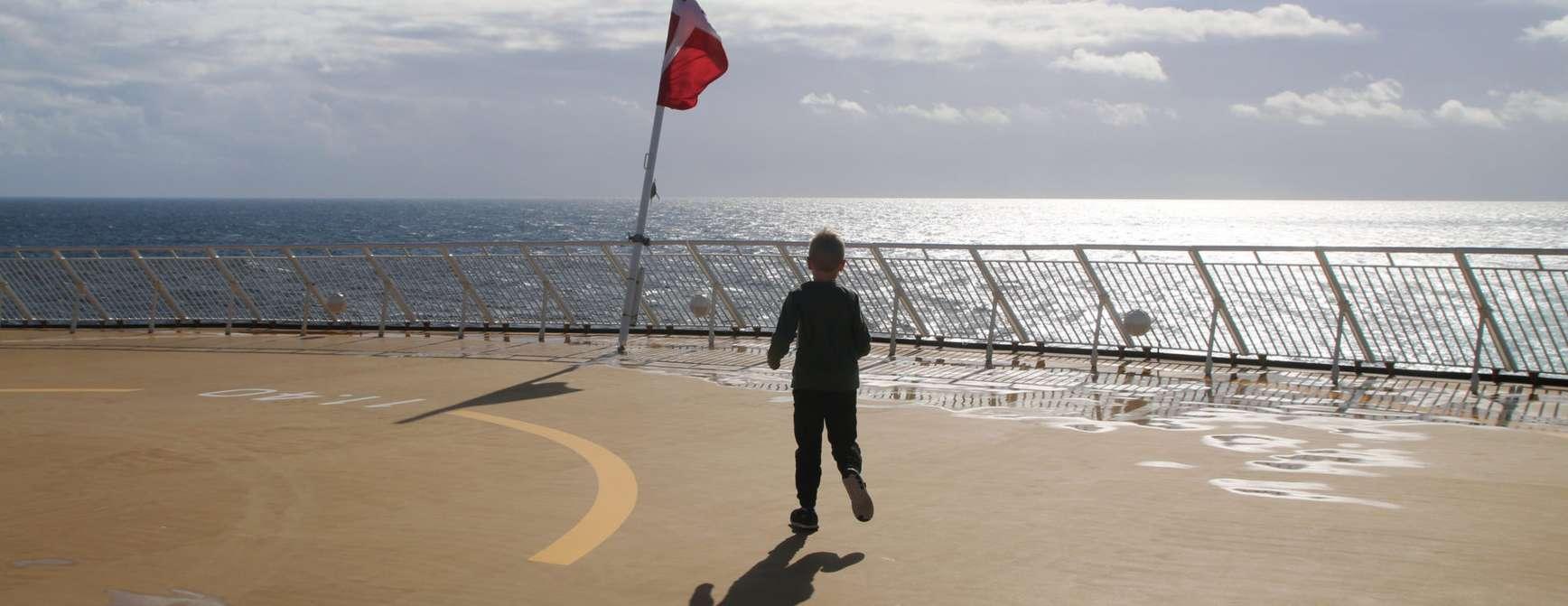 Gutt som løper på dekket av et skip