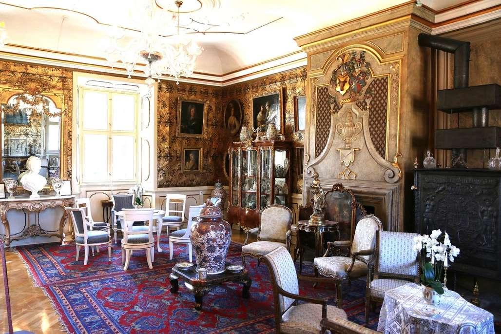 Gullsalen:Dette rummet har fått navn etter den gylne skinntapeten, som er laget av skinn fra villsvin nedlagt på Voegards eiendom. Det var Peder Reedtz som fikk satt opp gullskinnstapetet i 1750. Vasen på bildet er en ekte Ming, og i vitrineskapet bak i bildet står Marie-Antoinette og Ludvig XVIs private service framme. Kaminen til høyre er norsk og produsert i Larvik på 1800-tallet. Foto: Flemming Hofmann Tveitan/Fjord Line