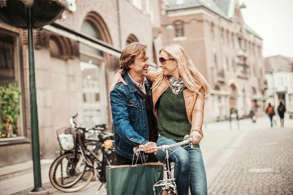 Par nyter lykken på sykkel på shopping i storby i Danmark