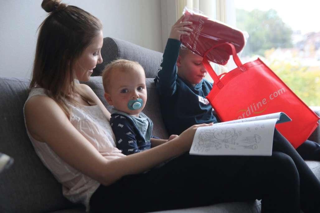 Mor og ta barn sitter i sofaen og ser på overraskelser.