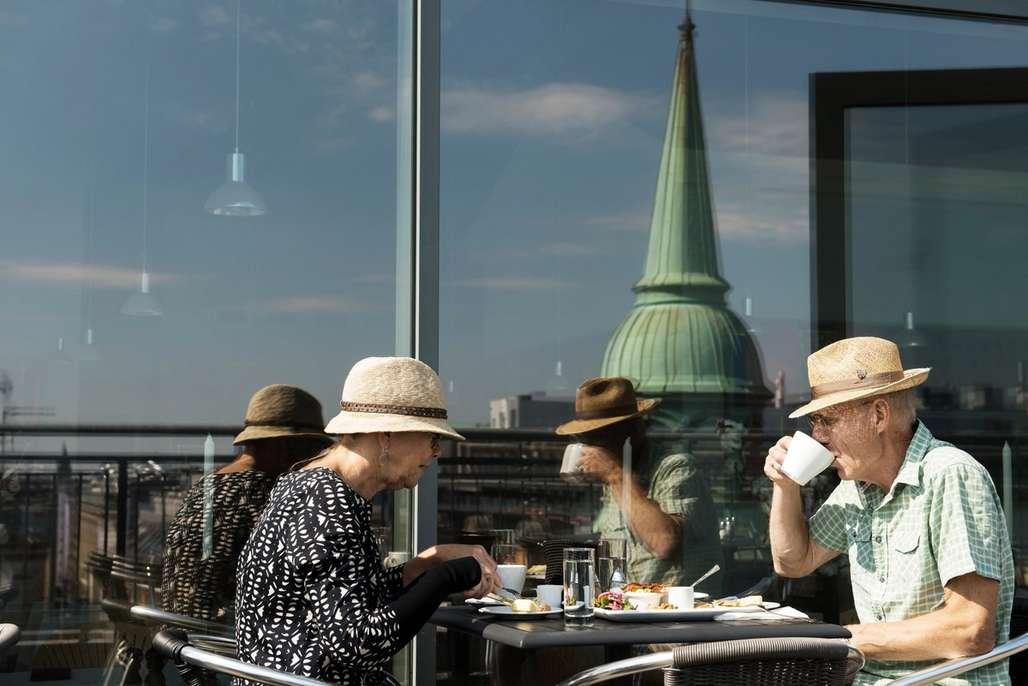 Liv i gatene: I Aalborg er det tett mellom stedene du kan sette deg ned, ta en pust i opplevelsesbakken og bare se på folkelivet. Foto: Visit Denmark/Robin Skjoldborg
