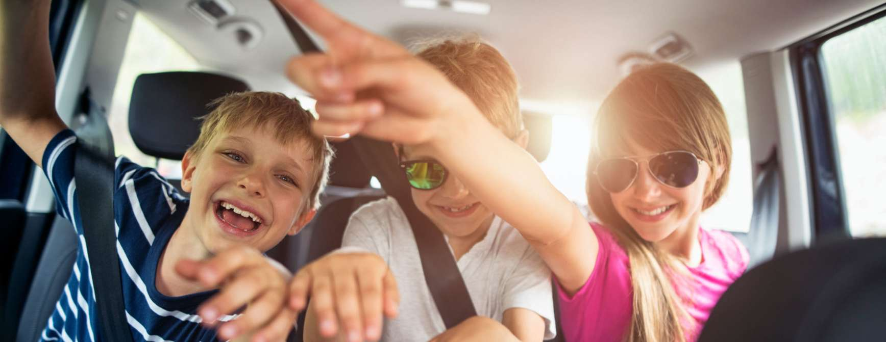 Tre barn i baksetet på en bil.