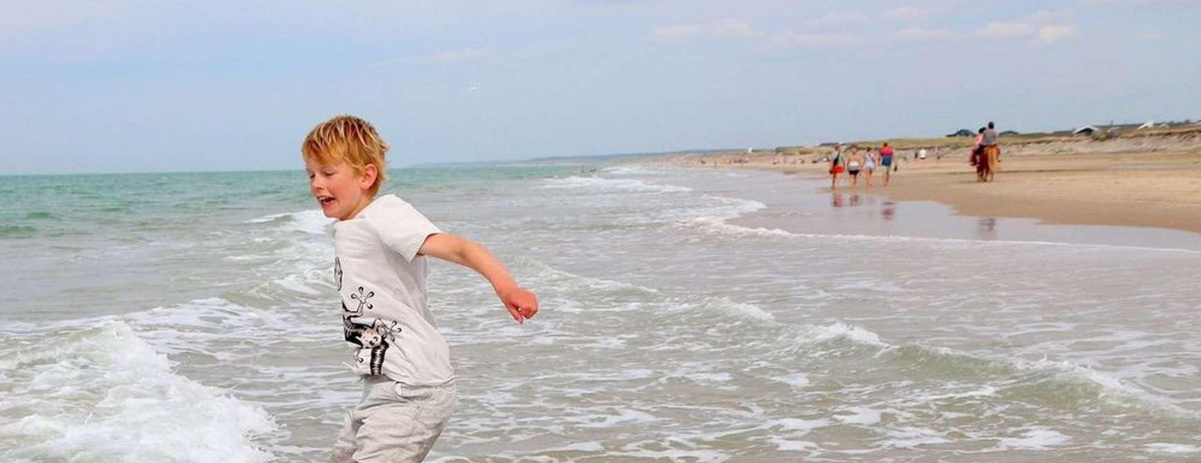 Barn leker i bølgene på stranden ved Skallerup