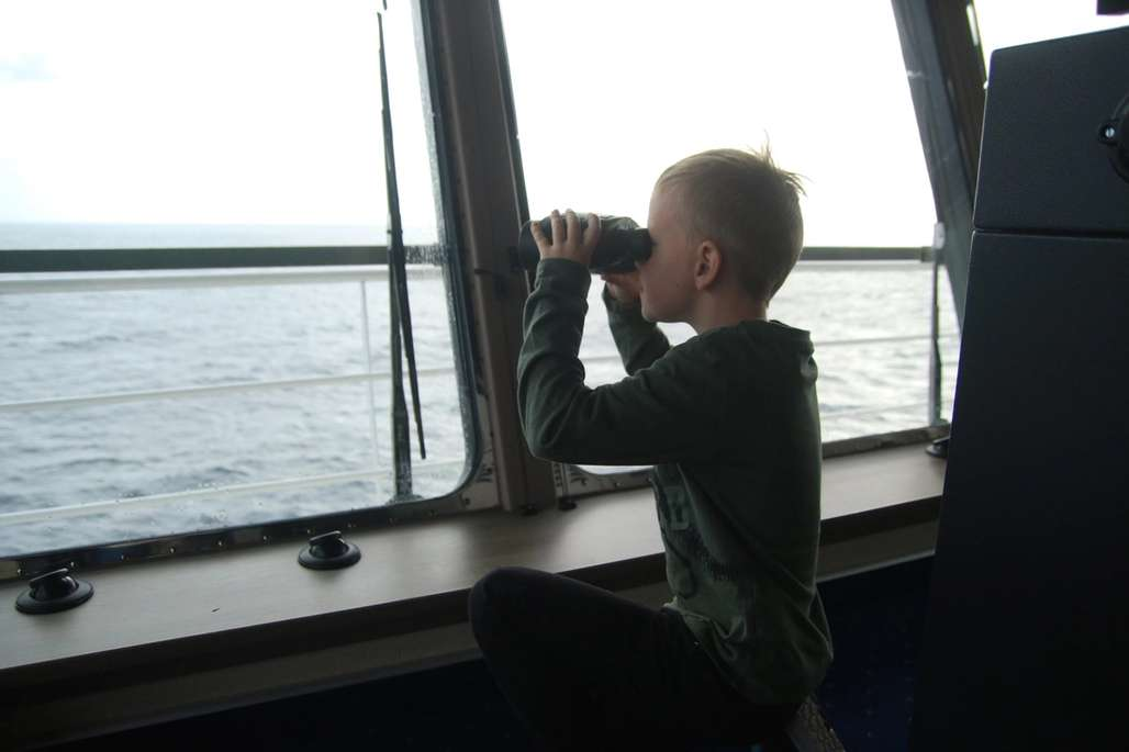 Gutt kikker i kikkert utover havet.