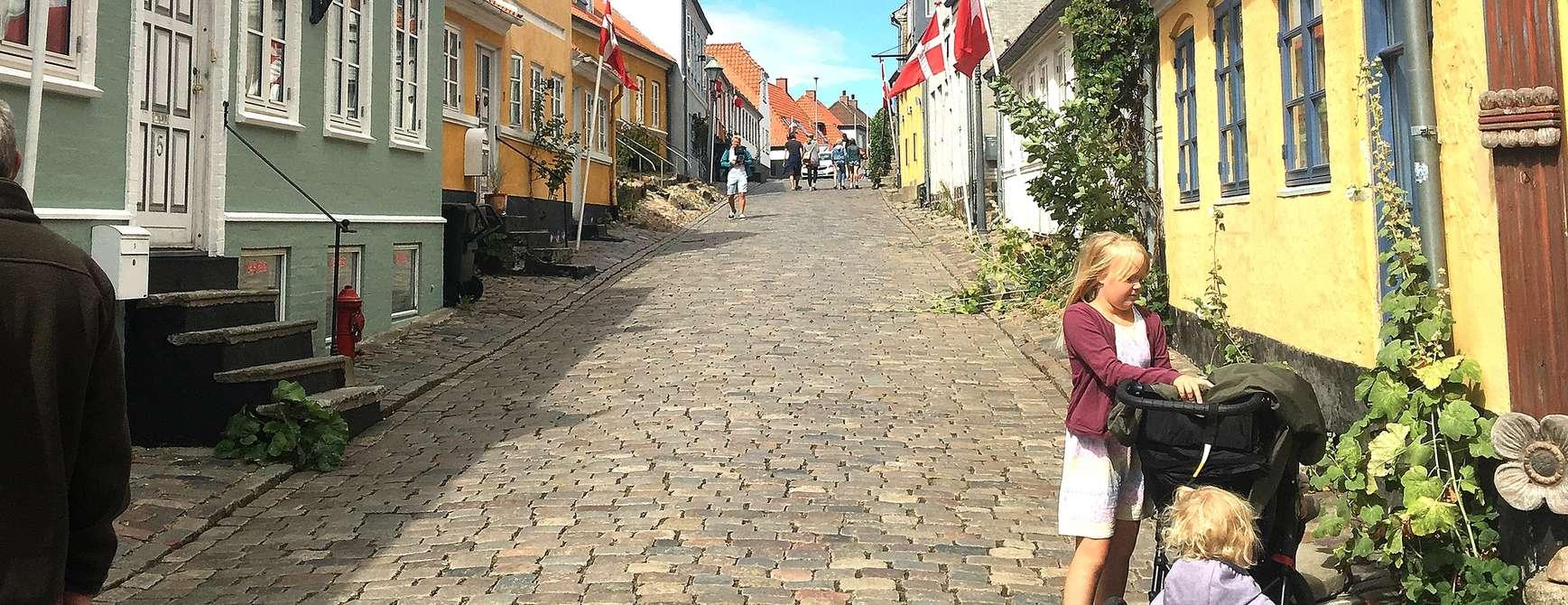 Familie nyter livet i en av de mange koselige brosteinsgatene i Danmark
