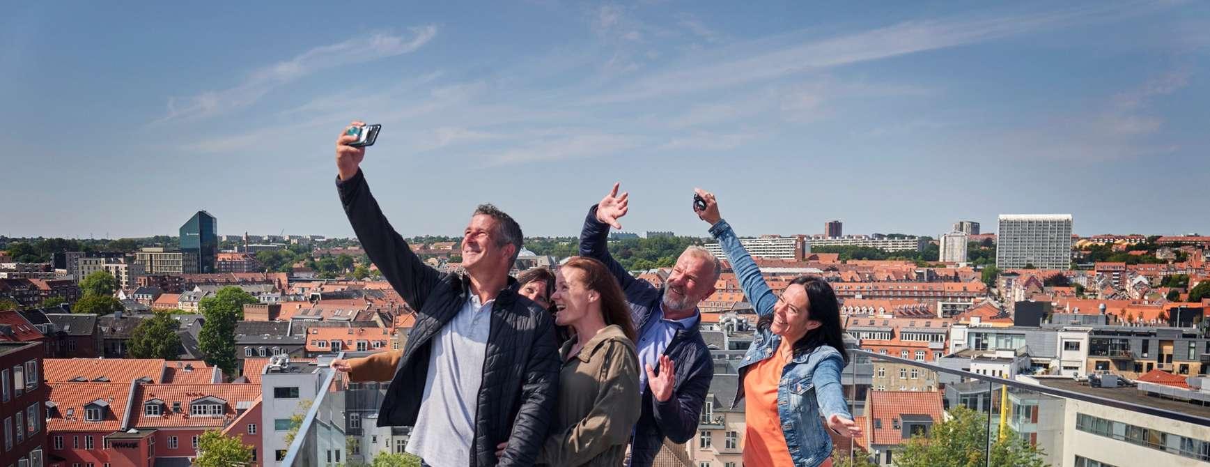 Vennepar nyter utsikten på taket av Aarhus