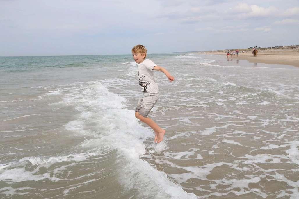 Milelange sandstrender med hoppende gutt.