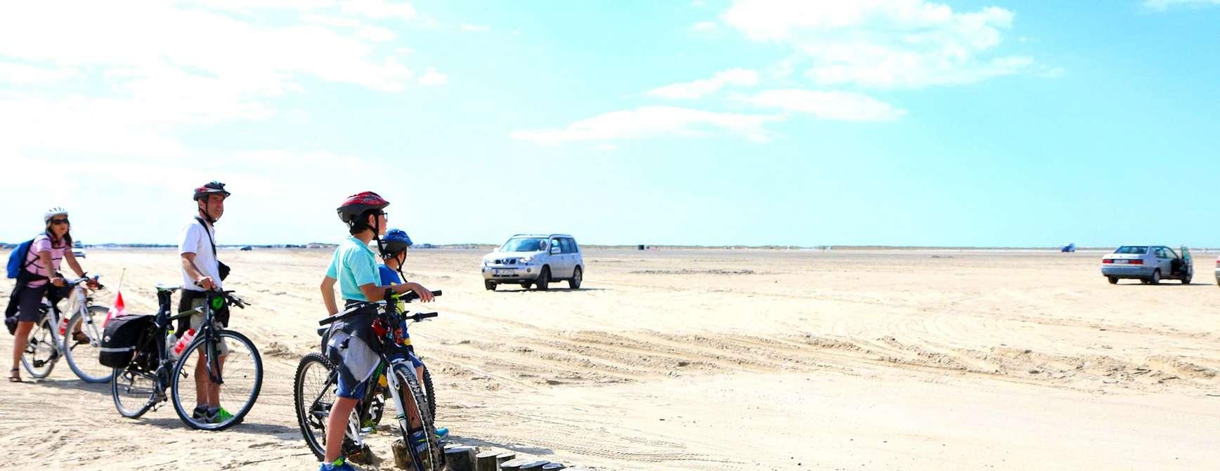 Langsstrakt strand med sykler, biler og folk
