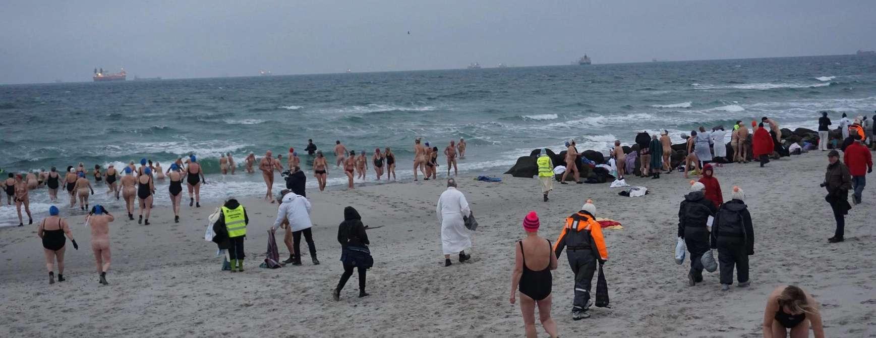 Strand om vinteren med mange badegjester.