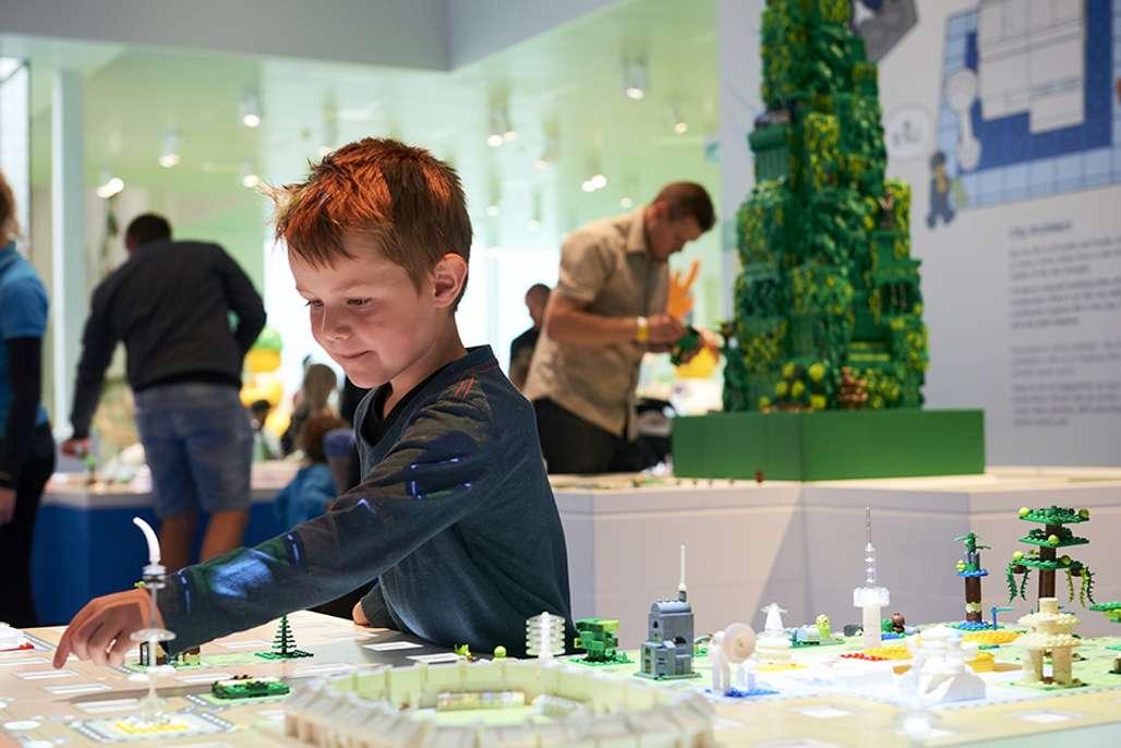 Gutt som leker med lego i Lego House