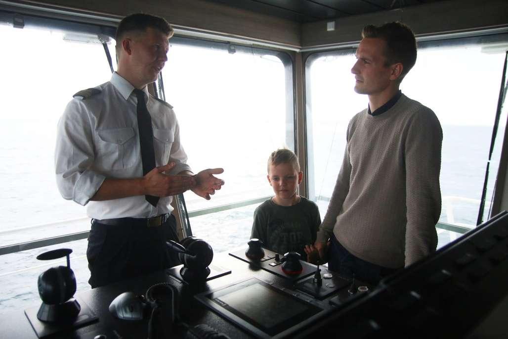 Førstestyrmann, gutt og hans far på brua på et skip.