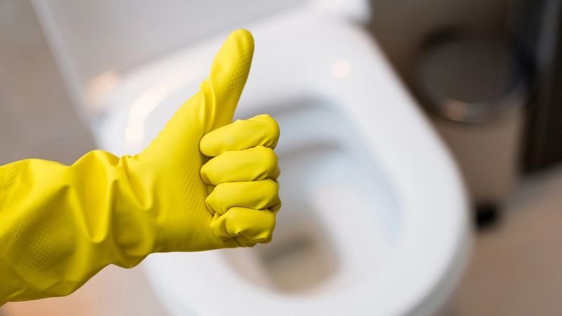 Hand in yellow rubber glove showing-thumb-up-sign above a white toilet bowl