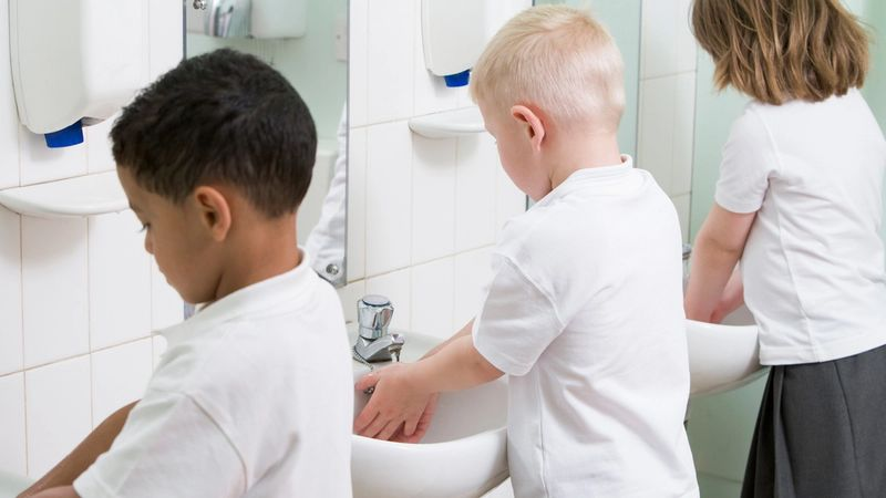 Three young children wash their hands in the sink at school