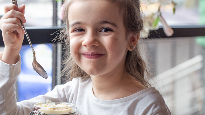 A young girl smiling and eating a dessert