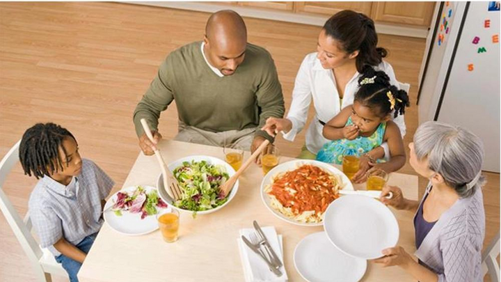 """""""Mother & father serving two children dinner at table"""