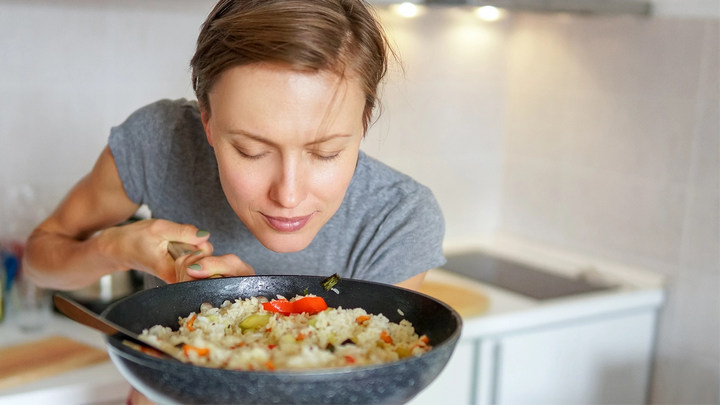 A woman savouring the aroma of a pan of rice and vegetables
