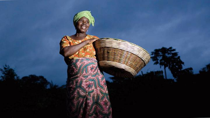A smiling woman carrying a basket against an African sunset