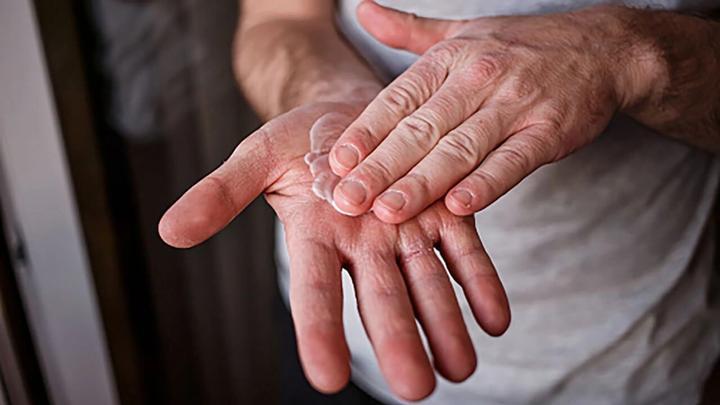 A person rubbing cream into their hands