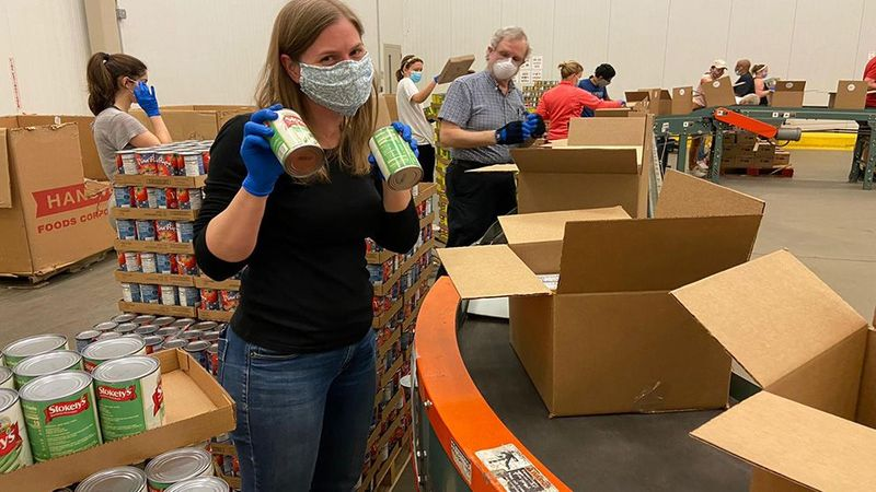 Woman packing items for United for America, an initiative designed to support communities in need during Covid-19.