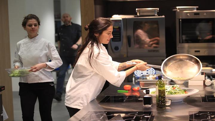 Women chef in industrial kitchen creating and serving a plant-based dish