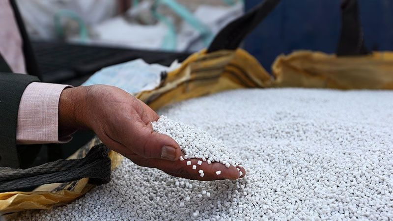 man holding plastic pellets in his hand