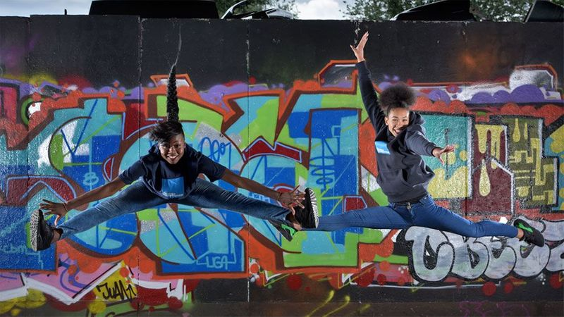 Two girls jumping in the air with their arms and legs outstretched in front of a wall covered with colourful graffiti.