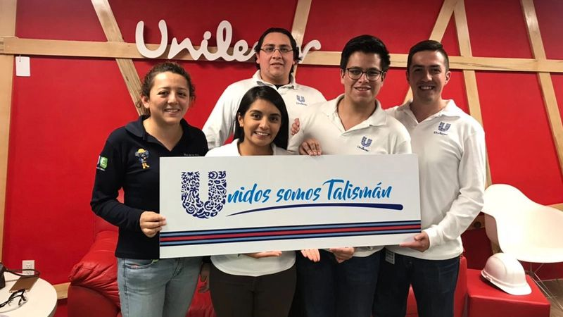A diverse group of Unilever employees holding a Unilever sign in front of a red wall