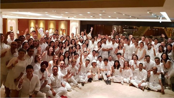About 50 people from Unilever International team pose for a group photo in an event space