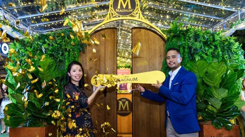 people posing at the entrance of magnum pleasure garden