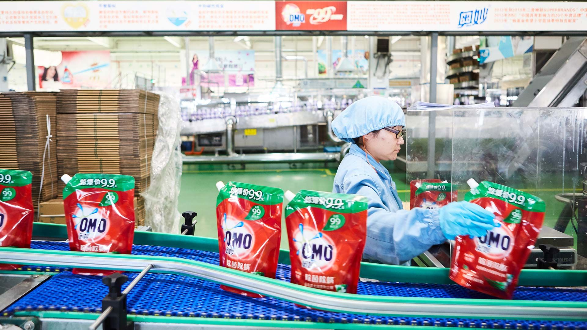 A lady wearing unilever uniform in a factory manning a line producing OMO laundry detergent