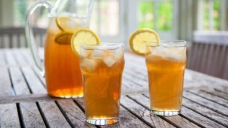 Picture of 2 glasses of iced tea with lemon along with a pitcher of iced tea