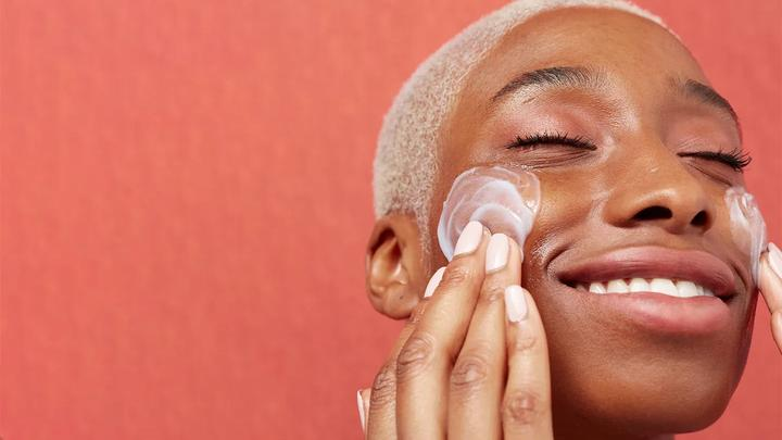 Woman smiling and moisturising her face