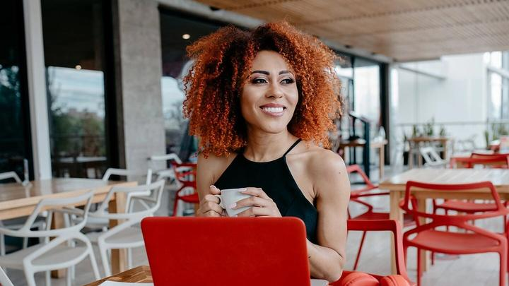 Smiling women with natural curls working on her laptop