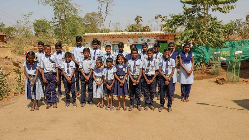 A group of 21 schoolchildren pose for a photo outside their school toilets in India
