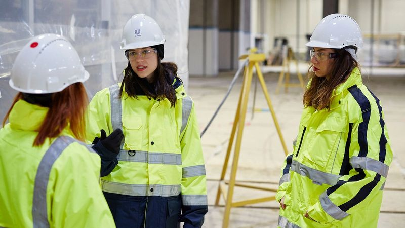 Three women in hard hats and high visibility jackets discuss a construction project at our factory in Turkey