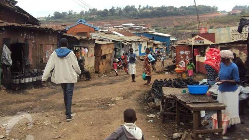 Street scene in the Mukuru slum, showing humble dwellings with roofs of corrugated iron