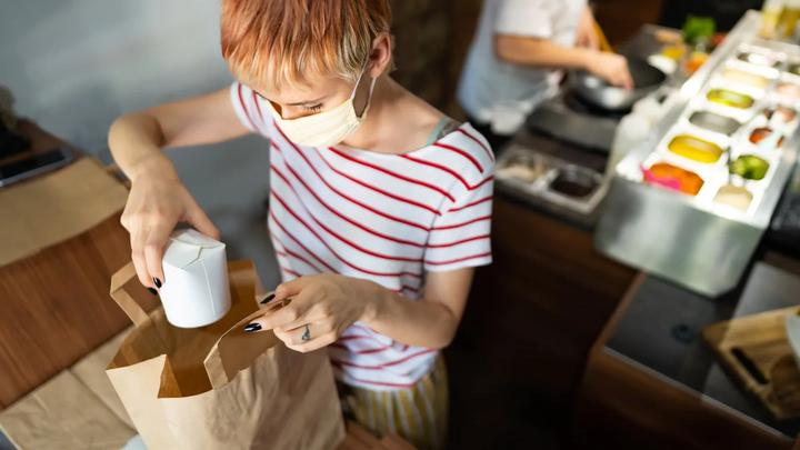 Woman kitchen worker packing food container into a takeaway bag with a chef preparing food in the background.