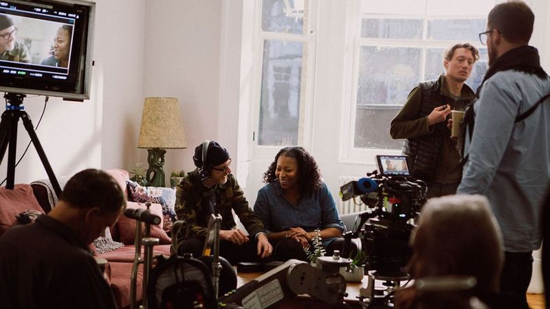 A film crew is taking a break in a light-filled living room with camera equipment on a low table and a screen on a tripod.