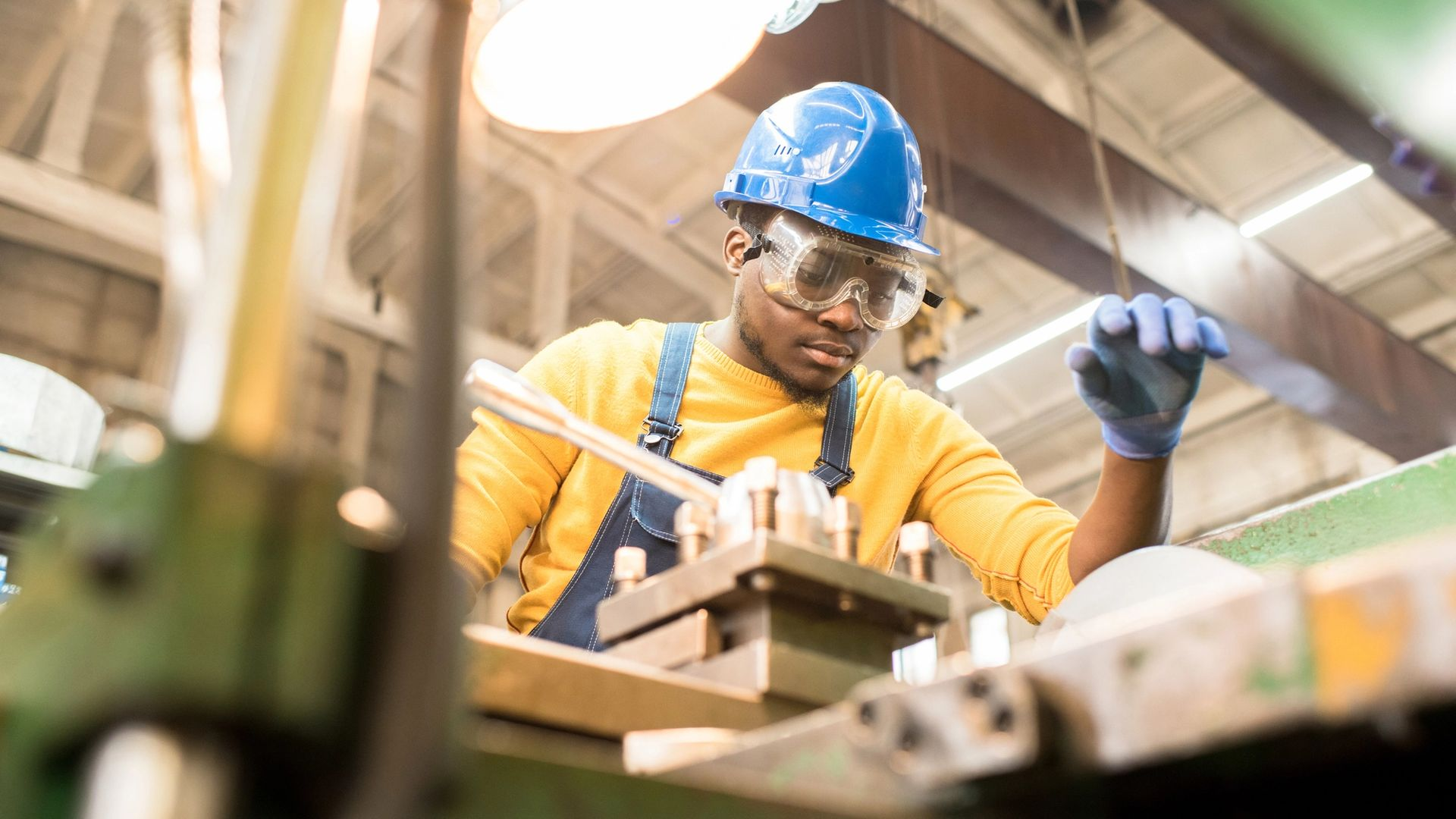 Man wearing hard hat and safety glasses working at a machine in a workshop